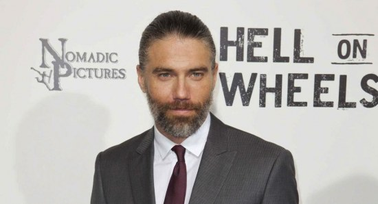 Anson Mount at press junket in grey suit