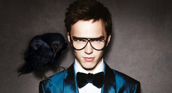 Nicholas Hoult in suit with glasses and falcon