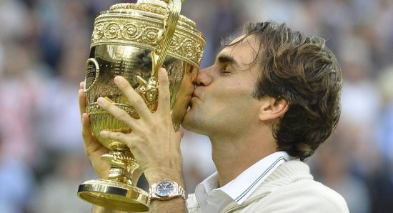 Roger Federer with one of his many Wimbledon trophies
