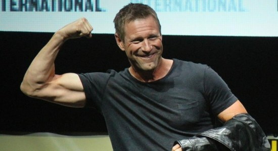 Aaron Eckhart showing the biceps